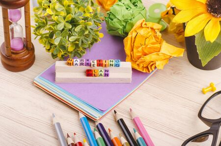 Business Campaign Concept background, colorful cube with word MARKETING PLAN on wooden desk