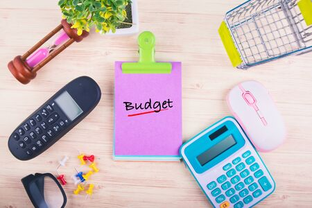 Financial or budget planning concept,top view of notepad with word BUDGET, mobile phone, calculator, and other accessories on wooden background