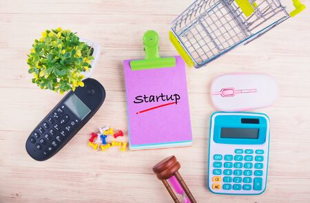 Starting new business concept,top view of notepad with word STARTUP, mobile phone, calculator, and other accessories on wooden background