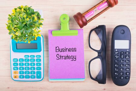 Business marketing concept, BUSINESS STRATEGY written on notepad on wooden desk