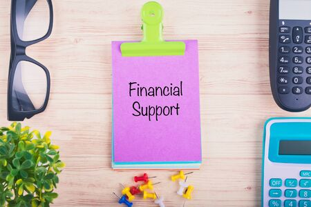 Business concept background, workplace with word FINANCIAL SUPPORT written on notepad