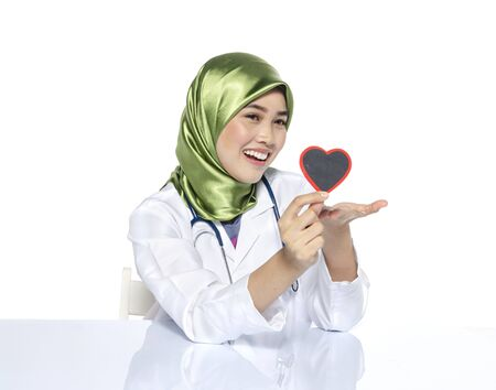 Young doctor with hijab. happy face expression siiting in front laptop ideal for stress management concept.