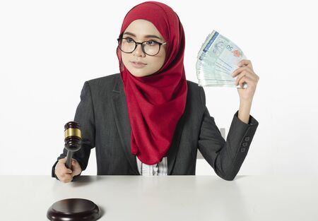 Auction bidding or judicial system corruption concept,portrait of young woman in hijab holding money and judge gavel.