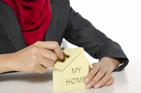 cropped image, young woman saving money for her new home against white background