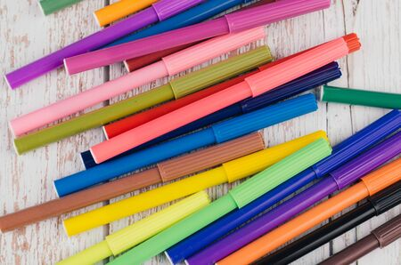 Back to school and offices stationary concept, stack of colored pens markers on wooden desk Foto de archivo