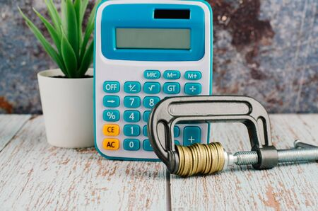 financial crisis concept, calculator and stacking coin squeezing in a G-clamp on wooden desk 写真素材 - 142145615