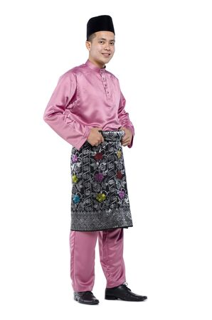 Portrait of young muslim with malaysian traditional attire called baju melayu standing against white background