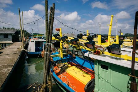 Beautiful view at Traditional fishing village with lovely sky and fishing boat moored near the shore