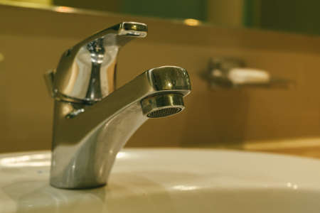 chrome water faucet in the modern bathroom. selective focus shot