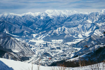 view from top mountain, white snow and beautiful landscape during winter season in Japan against blue sky background