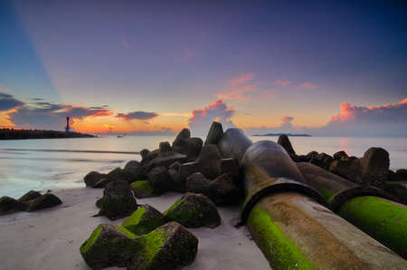Beautiful scenery during sunrise at tropical beach against golden sky and cloud balckground