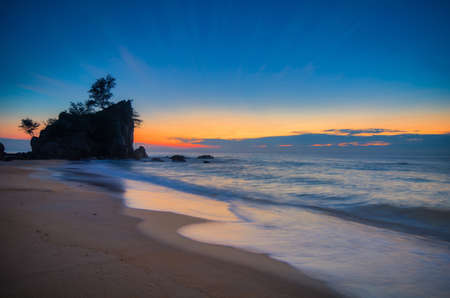 Beautiful scenery during sunrise at tropical beach against golden sky and cloud balckground Stock Photo - 153781327