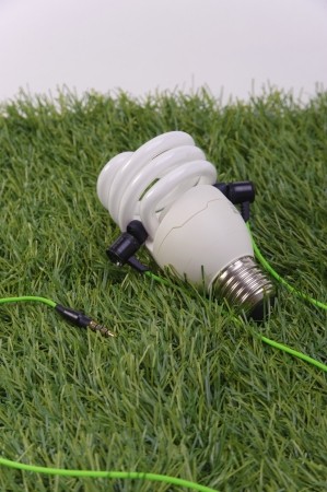 Compact Fluorescent Lamp with green earphones on grass patch Stock Photo - 21601841