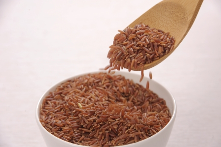 Bowl of brown rice with wooden spoon photo
