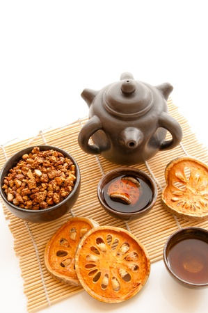 Slices of dried bael fruit, dried grain bael in a cup with china teapot and cups of bael tea  photo