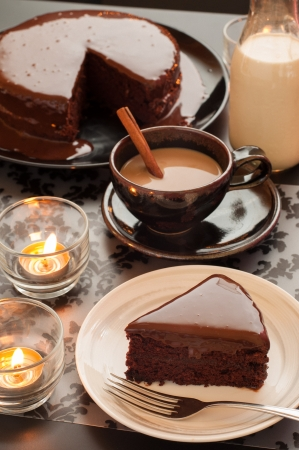 Sweet chocolate cake dessert, cup of coffee, bottle of milk and candlelight on the table  photo
