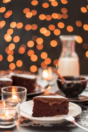 Still life of chocolate cake cup of coffee and bottle of milk with blurry christmas lights