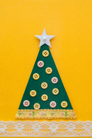 Handmade green Christmas tree on yellow background  photo