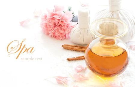 herbal massage ball: Spa still life with bottle of aromatic essence oil, herbal massage ball and carnation flower