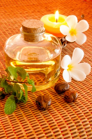 Bottle of aromatic essence oil and fresh frangipani  photo