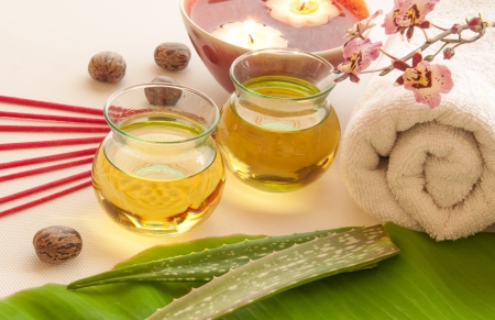 Health spa, two bottles of essential oil with fresh aloe vera, towels, candle, incense, one with orchid flowers  photo