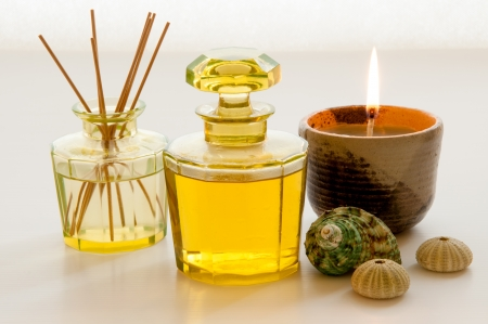 Aromatic essence oil bottle with bottle of fragrance reeds diffuser, candle and shells  photo