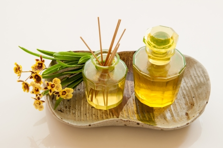 Aromatic essence oil bottle with bottle of fragrance reeds diffuser and bunch orchid flower