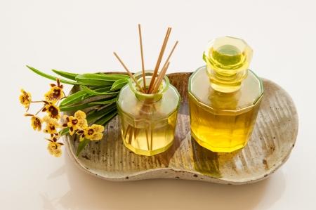 Aromatique bouteille d'huile d'essence avec une bouteille de roseaux de parfum diffuseur et bouquet de fleurs d'orchidées