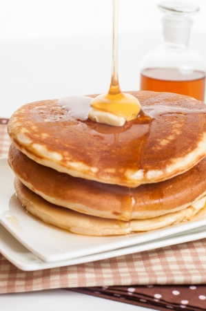 topped: Pancakes topped with butter and maple syrup  Stock Photo