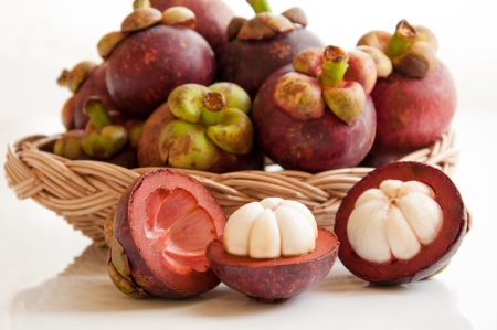 Fresh mangosteens fruit and cross section showing the thick purple skin and white flesh of the queen of fruits  photo