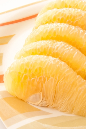 Slices of pomelo fruit on dish. photo