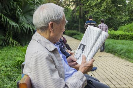 book jacket: An elderly reading a magazine in a park