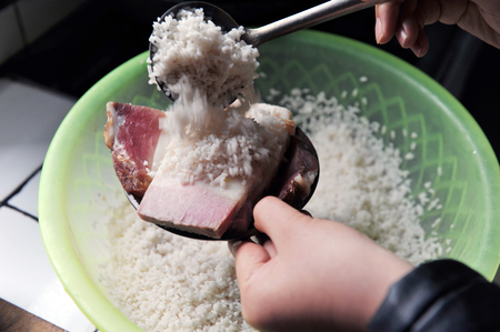 Scooping rice into a bowl with pork belly slices Stock Photo