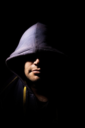 cowl: portrait of a man with a cowl covering his eyes. studio lighting. half face illuminated, half face in shadows. Stock Photo