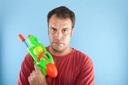 water gun: serious man with toy gun Stock Photo