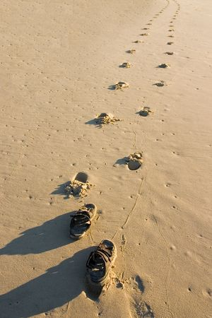 easygoing: Walking sandals and footprints on the beach