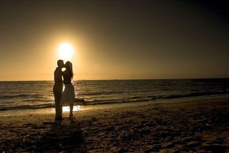 pareja besandose: Silueta de joven besar a la puesta del sol  Foto de archivo