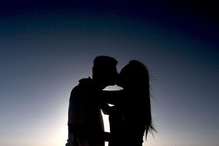 adore: Silhouette of couple kissing Stock Photo