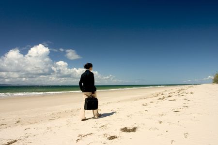 Woman with black suitcase walking along the beach photo