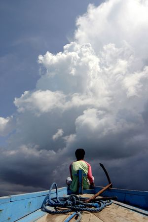 rainclouds: Indonesian fisherman watching big clouds coming towards him..
