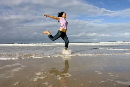 Happy female running around on the beach Stock Photo - 240423