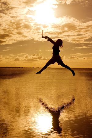 A silhouette of Woman holding a laptop computer jumping around photo