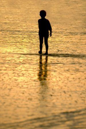 walking alone: Ni�o caminando solo en la playa