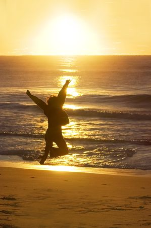 Woman jumping at sunrise photo