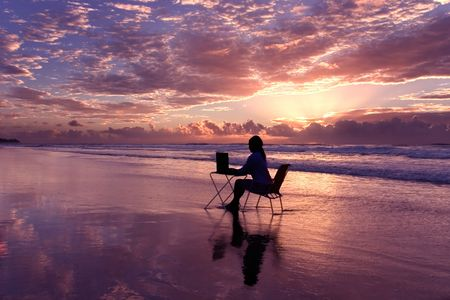 Woman with laptop working at sunrise photo