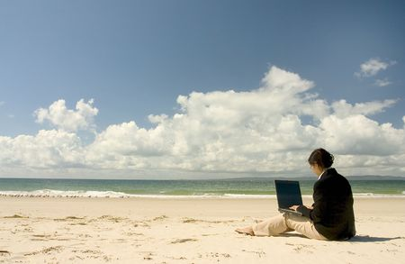 Businesswoman with business suit working at the beach photo