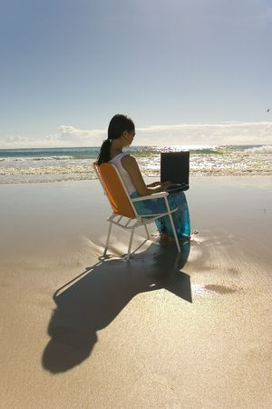woman with laptop working at the beach