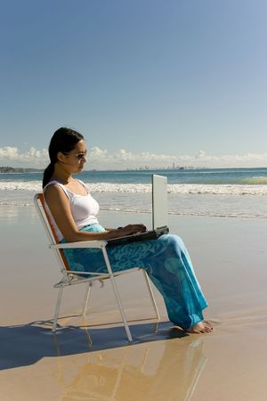 woman with laptop working at the beach photo