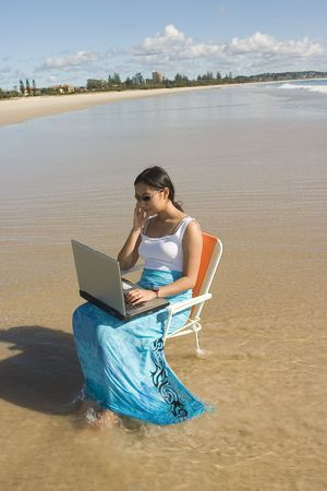 goldcoast: Asian woman with sun glasses Working at the beach Stock Photo