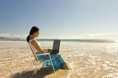 Asian woman with laptop getting wet.. photo